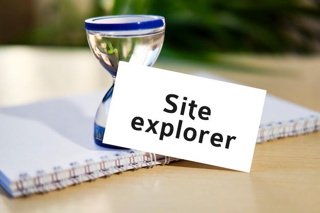 Testo di esploratore del sito web su un taccuino bianco e un orologio a clessidra