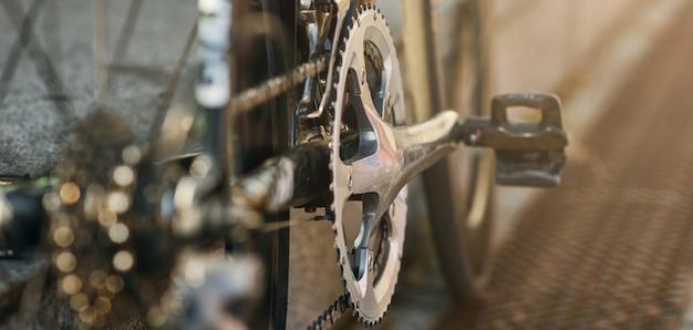 Intestazione del sito web di una vista dettagliata dei meccanismi della bicicletta, pedale della ruota dentata e catena su una montagna