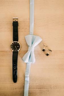 Accessori da sposa dello sposo: un papillon e scarpe marroni.