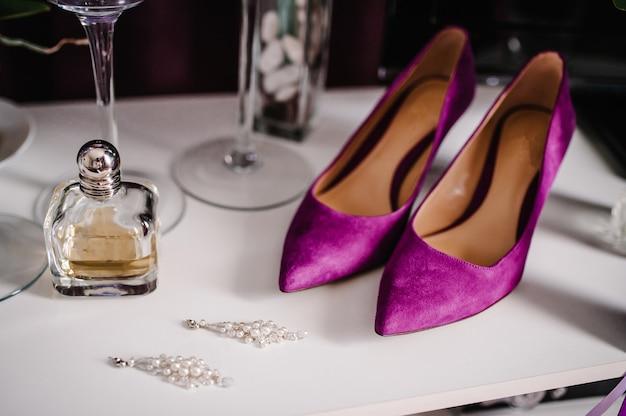 Accessorio da sposa sposa. scarpe, orecchini e profumi viola alla moda sulla tavola che sta sulla tavola di legno del fondo.