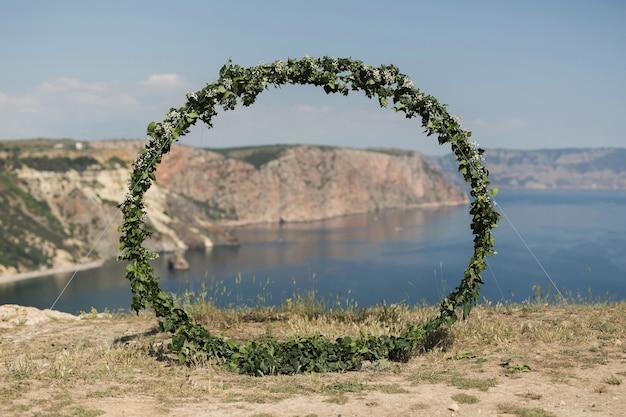 Arco nuziale a forma di anello su una scogliera sullo sfondo dell'oceano