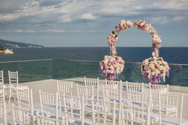 Arco di nozze con fiori freschi su uno sfondo di mare. vasi con fiori freschi.
