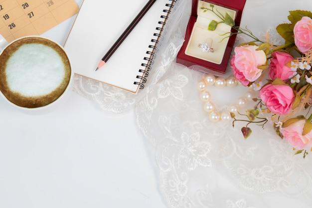 Fondo di nozze con la vista superiore del taccuino e della fede nuziale con lo spazio della copia