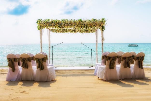 Matrimonio sulla spiaggia. arco di nozze decorato di fiori sulla spiaggia di sabbia tropicale.