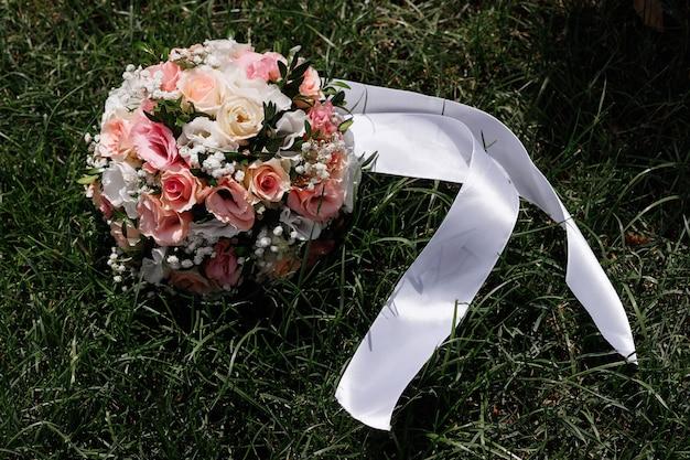 Bouquet da sposa della sposa sull'erba verde al sole