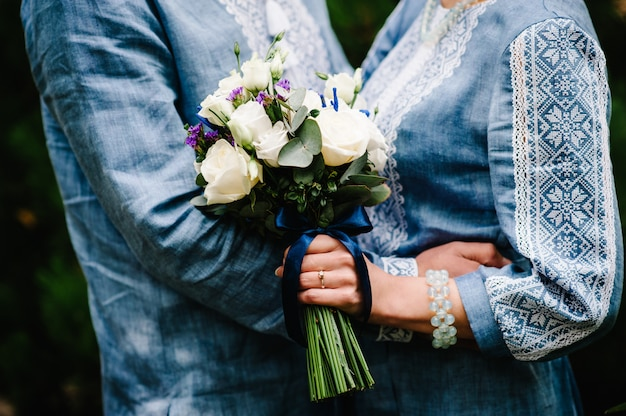 Fiori di bouquet da sposa di rose cespuglio, eustoma nelle mani, donna elegante spose che indossa un abito ricamato e sposo in camicia detiene un bouquet. cerimonia matrimoniale. avvicinamento.