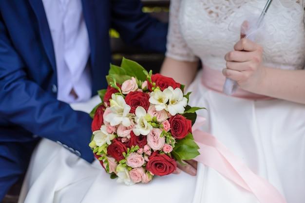 Mazzo di cerimonia nuziale in mani della sposa e dello sposo