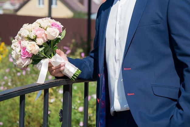 Bouquet da sposa nelle mani dello sposo