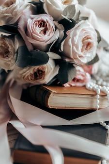 Un bouquet da sposa giace su un antico libro arancione tra nastri di raso rosa accanto a perline bianche
