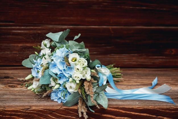 Bouquet da sposa sdraiato su una superficie di legno.