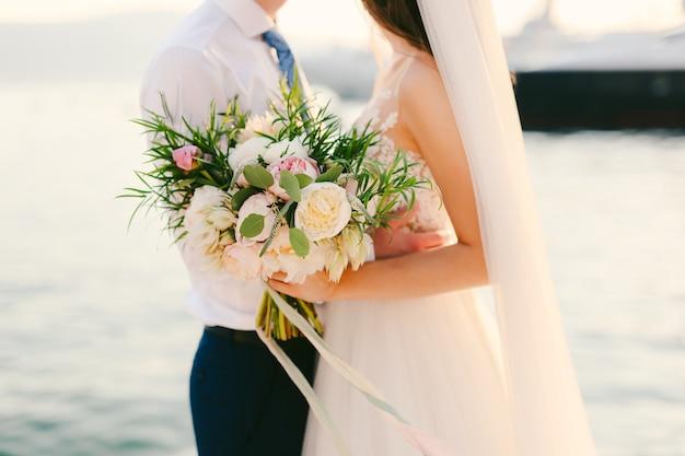 Bouquet da sposa di peonie nelle mani della sposa matrimonio in