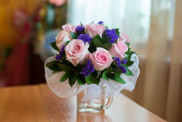 Bouquet da sposa di rose rosa in una grande tazza di vetro sul tavolo