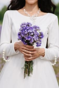 Bouquet da sposa di fiori di campo viola nelle mani della sposa sullo sfondo di un abito bianco