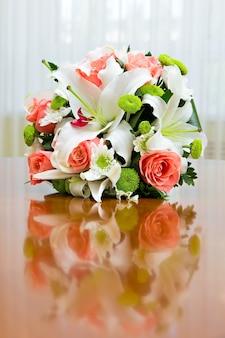 Bouquet da sposa di rose e gigli per la sposa a una festa di nozze. bouquet da sposa di rose e gigli sul tavolo sullo sfondo di una finestra luminosa.