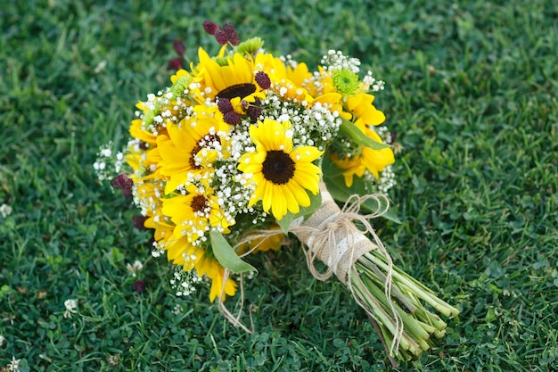 Bouquet da sposa di girasole sull'erba.