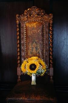 Un bouquet da sposa di girasoli giace su una sedia antica