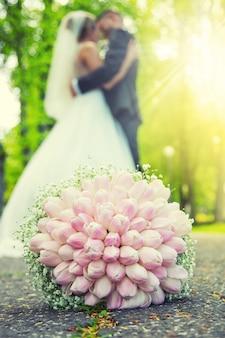Mazzo di nozze. bouquet da sposa steso per terra nel parco e sullo sfondo una giovane coppia in un romantico abbraccio.