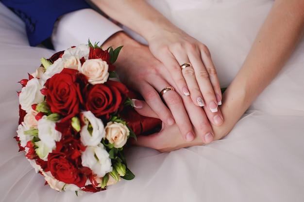 Bouquet da sposa con mani e anelli