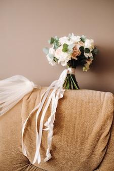 Bouquet da sposa con rose su una sedia e fiore all'occhiello