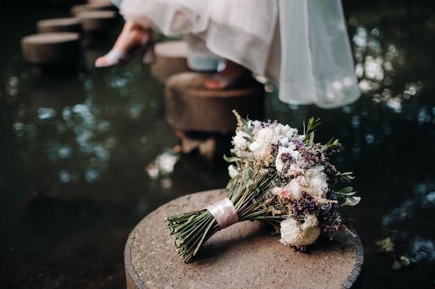 Bouquet da sposa con rose sul tavolo e un fiore all'occhiello