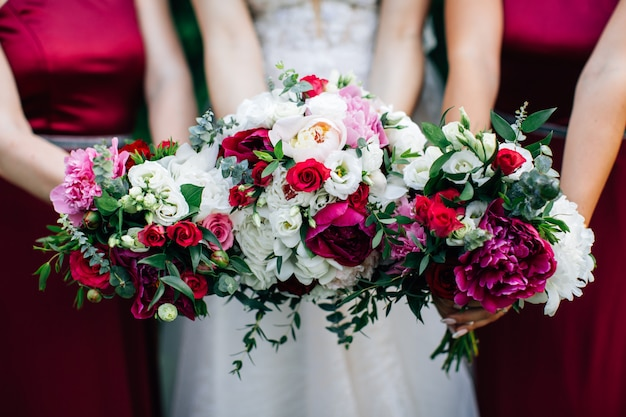 Mazzi di nozze nelle mani della sposa e delle damigelle. peonie viola e rose bianche