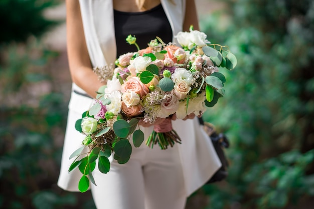 Bouquet da sposa di rose di diversi colori e primo piano di eucalipto nelle mani del wedding planner