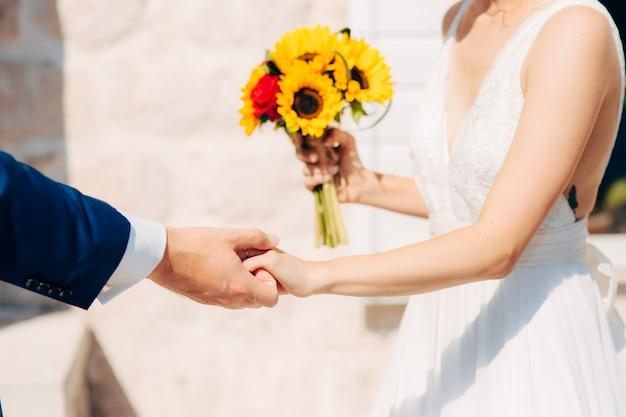 Matrimonio bouquet da sposa di girasoli nelle mani della sposa