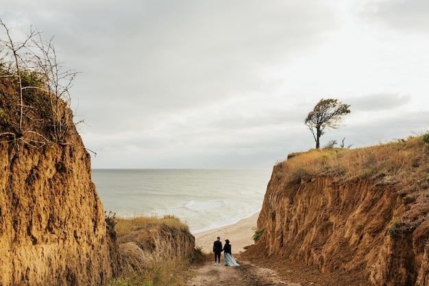 Matrimonio in riva al mare. giovani coppie felici sulla spiaggia vicino al mare.