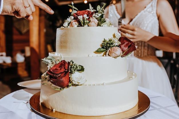 Torta nuziale al banchetto. gli sposi tagliano la torta alla festa