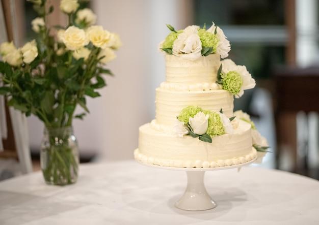 Torta nunziale decorata con i fiori su una tavola