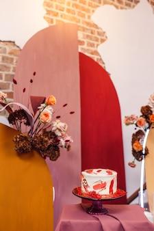 Torta nuziale vicino all'arco di nozze con fiori all'interno con pareti in mattoni.