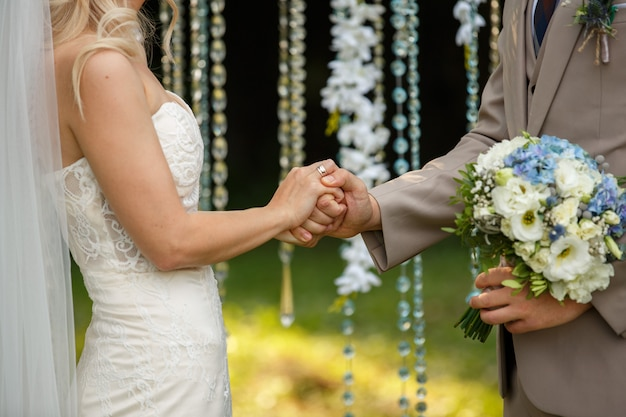 Cerimonia matrimoniale. la sposa e lo sposo stanno scambiando le fedi nuziali e stanno tenendosi per mano sull'arco di nozze