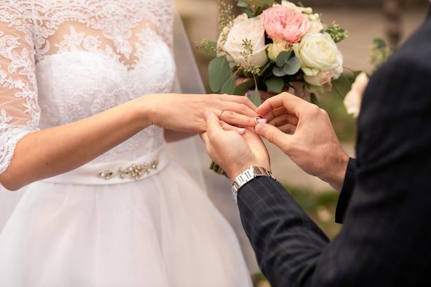 Cerimonia matrimoniale. lo sposo mette un anello nuziale al dito della sposa
