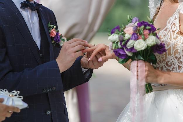 Cerimonia di nozze all'aperto vicino. lo sposo indossa l'anello nuziale della sposa. giorno del matrimonio. sposi emotivi si stanno scambiando fedi nuziali. felice coppia appena sposata.