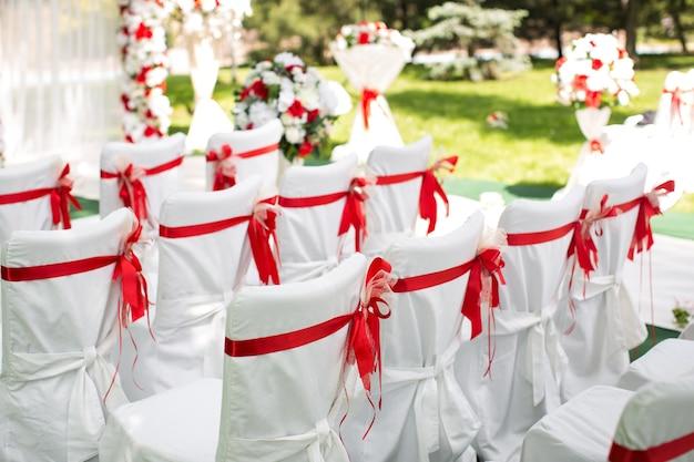 Cerimonia di nozze all'aperto. sedie bianche con nastro rosso.