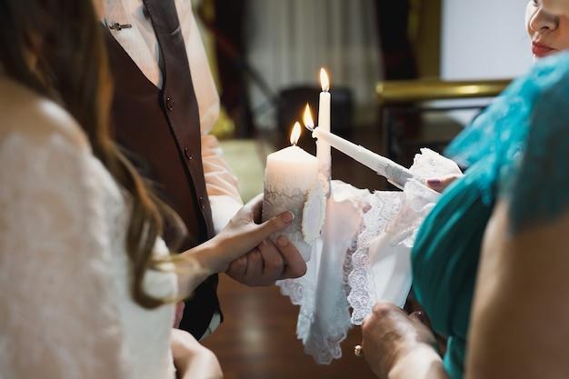 Cerimonia nuziale, accessori, gli sposi tengono in mano una grande candela