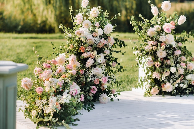 Cerimonia di nozze in strada sul prato verde.decorazioni con archi di fiori freschi per la cerimonia