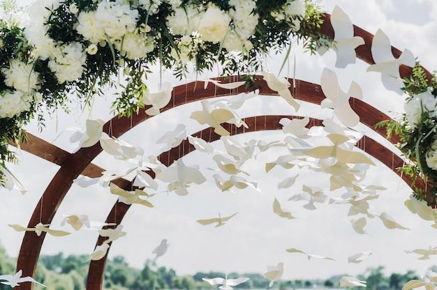 Cerimonia di matrimonio in strada sul prato verde.decorazione con archi di fiori freschi per la cerimonia.