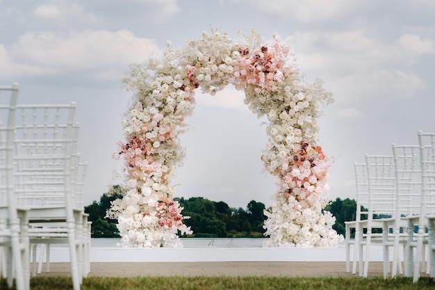 Cerimonia di nozze sulla strada sul prato verde.decorazione di una celebrazione del matrimonio