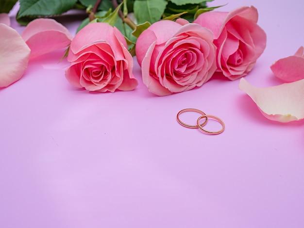Concetto di matrimonio. bella rosa rosa su sfondo rosa con due anelli di nozze. copia spazio.