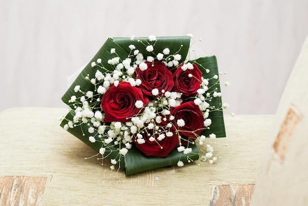 Concetto di matrimonio bouquet di rose rosse e anelli di nozze d'oro su sfondo pastello chiaro