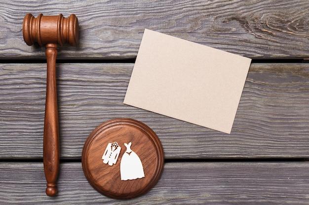 Concetto di matrimonio e copia spazio. martelletto in legno con costumi da sposa e carta bianca sul tavolo di legno.