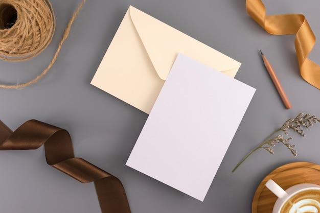 Un concetto di matrimonio. carta dell'invito di nozze su fondo grigio con il nastro e la decorazione.