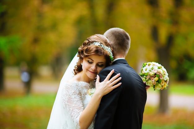 Sposi bella sposa e lo sposo. novelli sposi. avvicinamento. sposi felici sul loro abbraccio di nozze. sposo e sposa in un parco. vestito da sposa. matrimonio, autunno