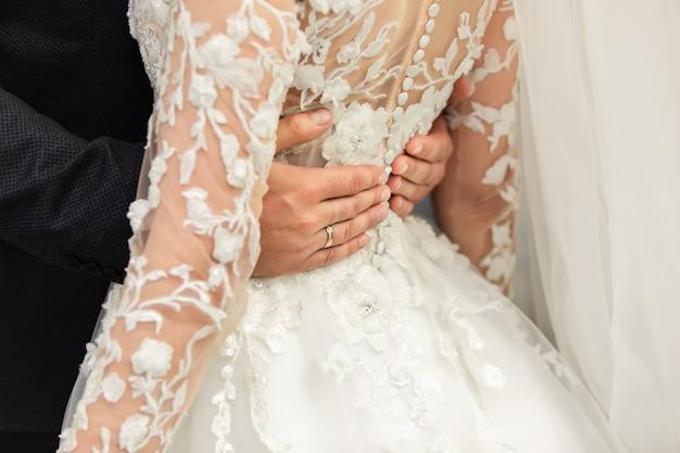 Tenersi per mano delle coppie di sposi, della sposa e dello sposo