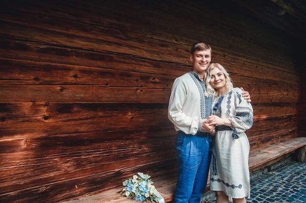 Sposi in una camicia ricamata con un mazzo di fiori sullo sfondo di una casa in legno
