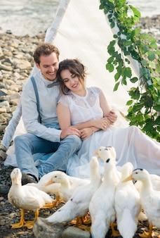 Coppie, sposo e sposa di nozze vicino all'arco di nozze su un fiume della montagna
