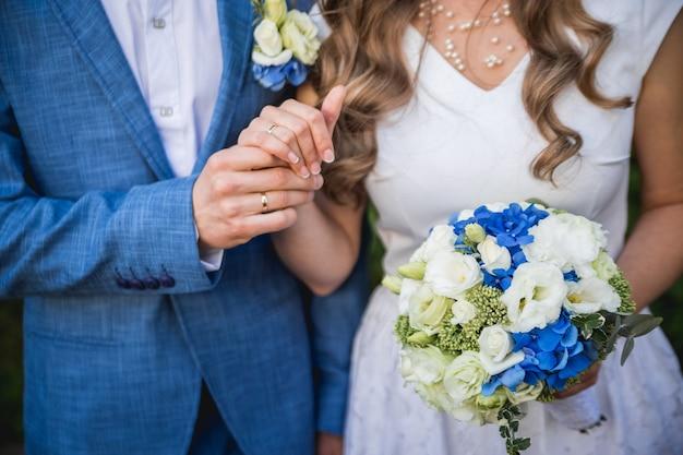 Sposi che si tengono per mano con un mazzo di fiori e fedi nuziali. dettagli del matrimonio.