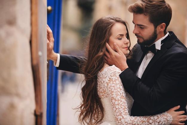 Coppie in viaggio di nozze che abbracciano nella città vecchia. porte vintage blu e caffè nella città antica sullo sfondo. sposa alla moda in abito lungo bianco e sposo in giacca e cravatta a farfalla. giorno del matrimonio.