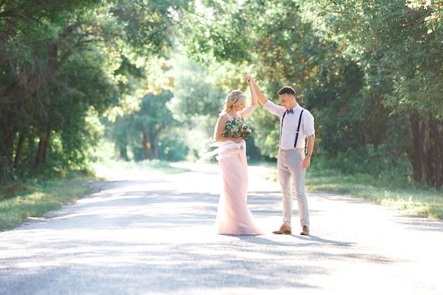 Sposi sulla natura nel giorno d'estate. la sposa e lo sposo che ballano
